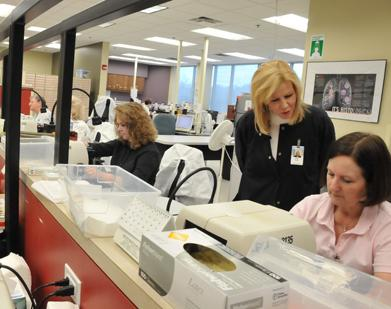 Lab manager Jeanie Meyers looks over Kay Nabers' work at Pathology Group of the Midsouth, which is located on Wolf River Boulevard in Germantown.