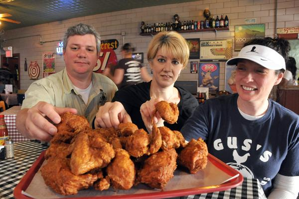 Matt McCrory, Mercedes Hawkins and Wendy McCrory prepare to dig into Gus's signature product. The McCrorys have purchased franchising rights for Gus's World Famous Fried Chicken.