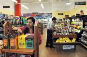 Hamida Mandani and Sunny Mandani stock goods in their City Market Groceries & Deli on Main Street in Downtown Memphis.