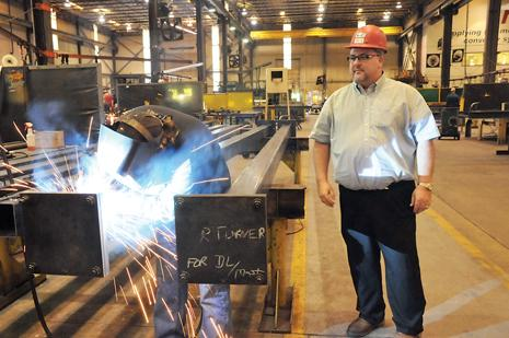NKC manager Gene Bloodworth watches Tracey Taylor weld a component of a conveyor system. The company has contracts with Toyota, Nissan and Honda manufacturing operations.