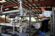 Gene Bloodworth, NKC's manager of manufacturing information systems, checks on a conveyor system component.