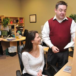 Accountant Brandy Liles and Matthew Patrick, managing member of Patrick Accounting and Tax Services, discuss the numbers of one of their clients.