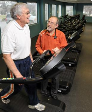 David Wright talks with patient Ken Wyatt as Wyatt works out on a treadmill. Wright has restructured his business, The Wright Clinic Inc., with positive results.