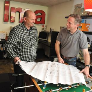 Douglas Leininger and Tim McCullough look over a client's architectural plans. Their company, LM Architecture, was formed when both were laid off from their jobs.