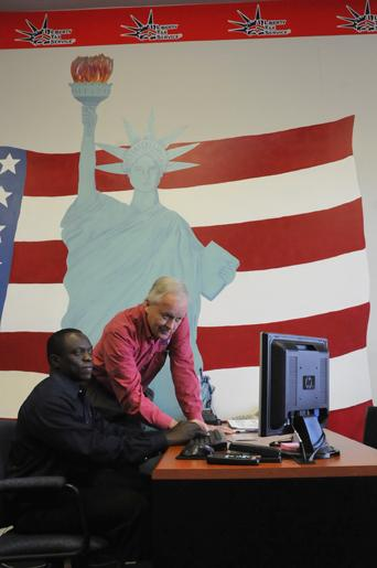 Numo Bah and Mike Conway of Liberty Tax Service are waiting for the Internal Revenue Service to program its system with new rules.