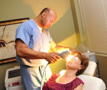 Rolando Toyos applies the Intense Pulse Light procedure, also known as DELIT, on patient Vicki Bland.