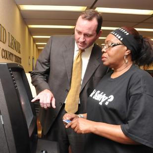 Shelby County Trustee David Lenoir assists Bertha Williams in making a  payment on her property taxes using a kiosk in the lobby of the  trustee's office.