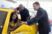 Henry Hutton (right) shows Ka'ren and Lamaar Chatman a new Camaro at Chuck Hutton Auto Group, where sales are up 16 percent over last year numbers.