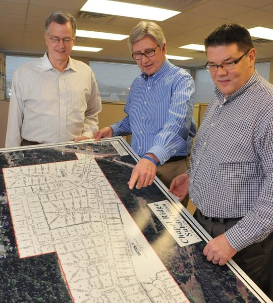 Bob Noell, Mario Lara and Bob Krypel look at the layout of Chapel Ridge, one of the condominium communities managed by their firm, Wright Property Management.