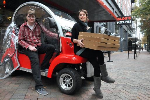 Brad Tedford and Brooke Brewer of Aldo's Pizza Pies get ready to deliver pizzas with the restaurant's new electric 'Bubble Buddy' vehicle.