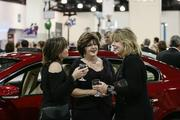 Partygoers mingled between the cars and trucks that will be featured at the auto show.