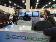 Auto show attendees try out a driving game.