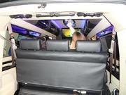 A loaded van including a flat screen television and track lighting.