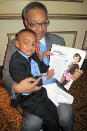 John Daniels Jr. of Quarles & Brady LLP with his grandson, John, holding up a copy of the story about his mom.
