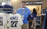 A Brewers employee holds up some of the merchandise available in the team's retail store.