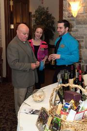 Craig Hauser from CJ & Associates Inc. talks with members of Mangold Creative LLC by the wine and chocolate raffle display.
