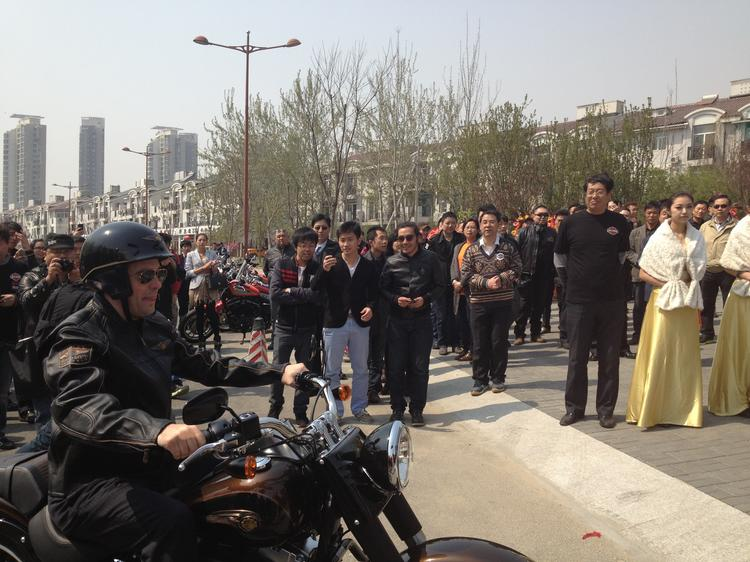 Chinese residents look on as Gov. Scott Walker rides a Harley-Davidson motorcycle at a dealership opening in Tianjin.