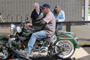 Passersby watch as Tim McLean revs the engine of a 2013 Softail Deluxe motorcycle.