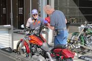 """Jerry Gagner, Harley-Davidson Museum facility maintenance manager, fills up the tank of a 2013 Dyna Wide Glide motorcycle while Tim McLean, a museum visitor experience associate, spiffs it up. The stock motorcycle is part of the museum's """"Jumpstart"""" program that lets visitors sit on the bike, which is fastened to the ground, and rev the engine to feel the motorcycle's power."""