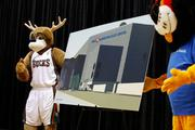Milwaukee Bucks mascot Bango (left) holds a rendering of the Bradley Center with the BMO Harris sign with the  bank's mascot Herbert.