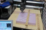 A CNC machine carves out a piece designed on a computer by a member of Milwaukee Makerspace.