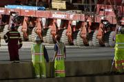 A large number of construction workers help guide the bridge into place.
