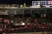 Construction crews worked on the bridge segment while it was put in place.