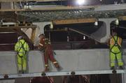 Workers help attach the bridge section.