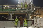 Safety-harnessed workers eye the bridge.