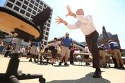 Danny Fochesato of JP Morgan Chase competes in the office chair push event on Monday at Red Arrow Park.