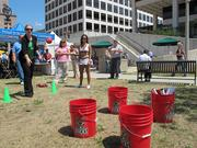 Jenny Vidal of Quarles & Brady LLP tosses a red ball into a bucket in a game led by Milwaukee Bucks cheerleaders.
