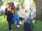 Penworthy Bear from children's book provider The Penworthy Co. waves to the crowd with Sammy the puppet and Alioto.