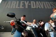 Jen Schreier of John Deere celebrates her 50th birthday by testingout a 2013 model Harley unveiled at the event.