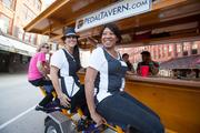 Elizabeth London, (center) a student of the Art Institute of Wisconsin, and Chanell Royston, an event coordinator of Fashion's Night Out, ride the Pedal Tavern between boutiques.