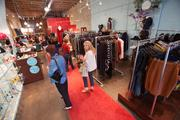 Customers check out the fashions at Lela Boutique.