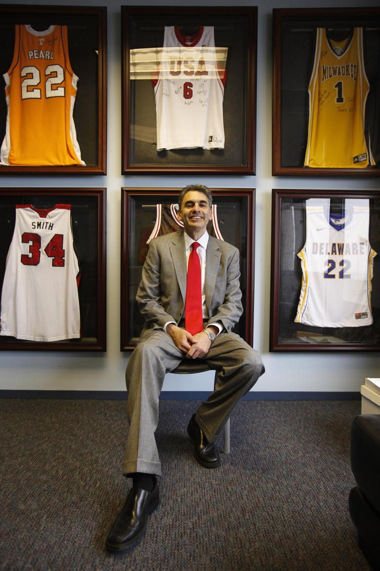 David Gruber surrounded by a gallery of basketball jerseys. Bruce Pearl's son Steven's Tennessee jersey (#22) is top left; Gruber's UWM booster jersey (#1) at top right, and Gruber's Delaware jersey (#22) in honor of his playing days for the college at bottom right.