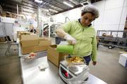 For small orders, Great Skott Foods employees like Veronica Hernandez hand fill containers for shipping.     Click here to read the story.