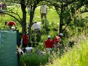 Volunteers and tournament officials search for a golf ball that ended up off the course.