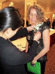 Forty under 40 winner Kathleen Montgomery, of Children's Hospital of Wisconsin, gets a corsage before the awards dinner.