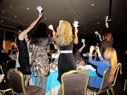 """Assisted by plastic """"clappers,"""" guests cheer for their favorite winner."""