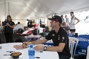 Driver Ryan Hunter-Reay signs autographs before the race in the Marcus VIP tent.