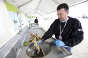 Racine-based InSinkErator provided food waste disposals. Jeff McMahon feeds in some of the more than 1,200 pounds of food ground up during the event.