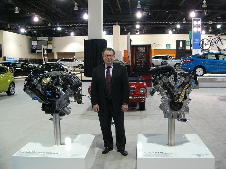 Jim Tolkan, president of the Automobile Dealers Association of Mega Milwaukee Inc., stands between two Mustang engines in the Ford exhibit.