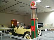 A gravity gas pump from 1925 stands next to a 1926 Chevy touring car.