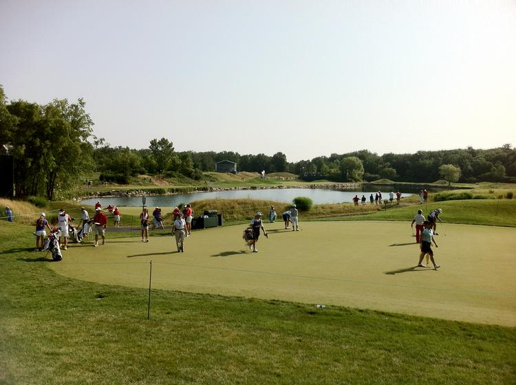 Fans watch golfers practice putting on Friday morning at the U.S. Women's Open in Kohler.