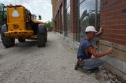 A builder works on the exterior masonry.