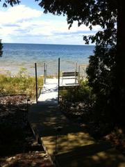 The beach house has 100 feet of frontage on Green Bay and a long pier extending out into the water.