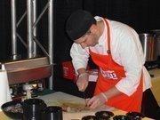 Sanford chef de Cuisine Justin Aprahamian prepares food at the event.