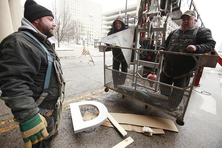 Crews work Monday on changing the sign at the Delta Center in downtown Milwaukee.