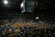 Marquette University students rush the court after a big win by the men's basketball team on March 8, 2003.